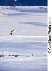 people doing kitesurfing on a frozen mountain lake