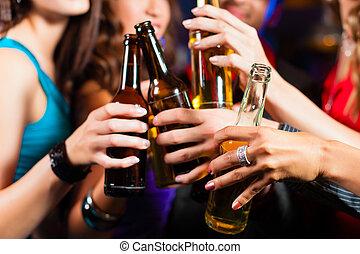 People drinking beer in bar or club