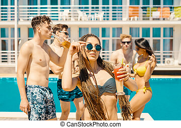 people drinking cocktails and beer during party at the pool