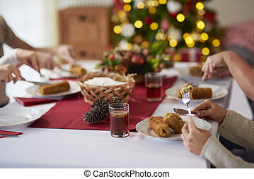 People eating croquette over Christmas table
