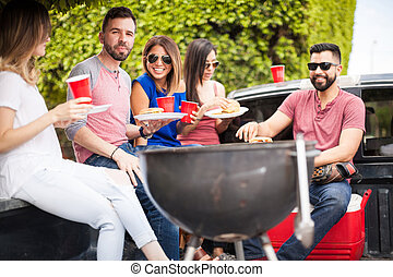 People eating hamburgers next to a grill