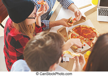 People eating pizza at workplace