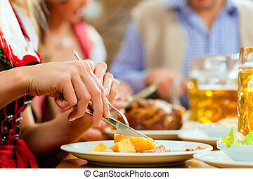 Inn or pub in Bavaria - group of young men and women in traditional Tracht drinking beer and eating roast pork with dumplings