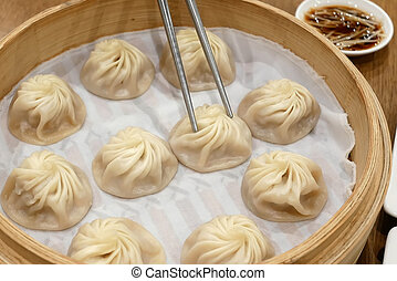 People eating soup dumpling buns with chopsticks in restaurant