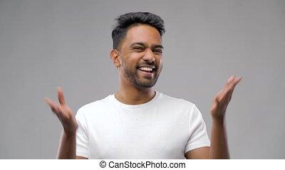 confused indian man shrugging shoulders - people, emotion...