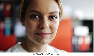 face of happy smiling middle aged woman at office
