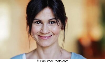 people, emotion and facial expression concept - face of happy smiling young woman