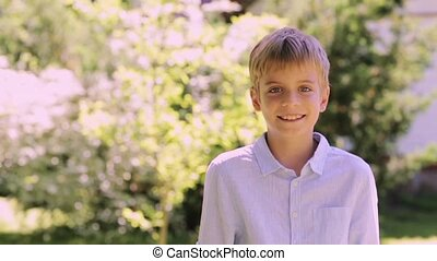 smiling preteen boy outdoors at summer garden - people,...