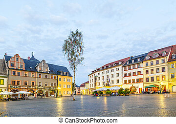 WEIMAR, GERMANY - MAY 27: people enjoy sunset at central market place on May 27, 2012 in Weimar, Germany. The houses around the market place are old historic originals from the 18th century.