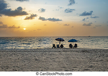 people enjoy the sunset at south beach, Miami