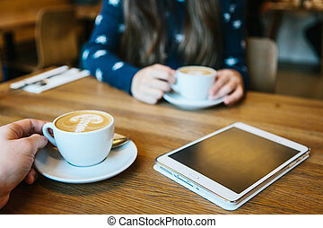 People enjoy their morning coffee in a cafe and communicate with each other. The tablet is on the table