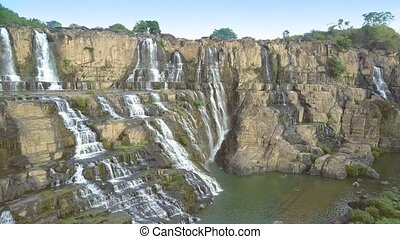 people enjoy waterfall sitting jumping on rocks standing...