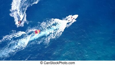 People enjoying boats and watersports with view from aerial flying drone in clear aqua blue sea water and blue sky