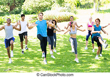 People exercising in the park - Group of multiethnic people...