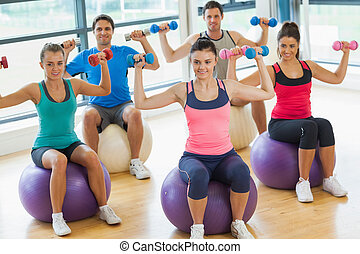 People exercising with dumbbells on fitness balls