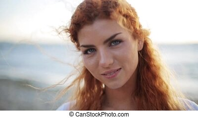 happy young redhead woman face on beach - people, facial...