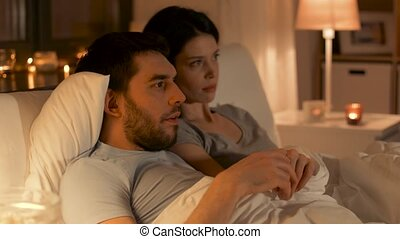 couple watching tv at night at home - people, family and...