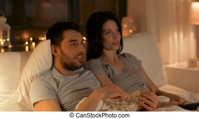 couple with popcorn watching tv at home