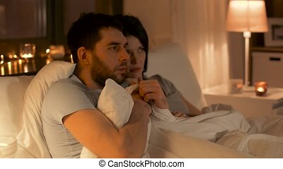 scared couple watching horror movie on tv at home - people,...