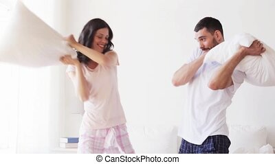 happy couple having pillow fight in bed at home