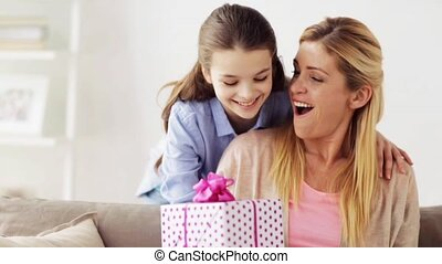 happy girl giving present to mother at home