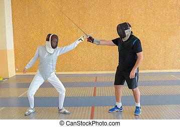 People fencing indoors