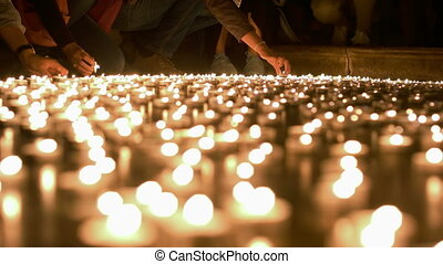 People Firing Up and Placing Candles to Other Ones