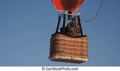 People flying in colorful hot air balloon