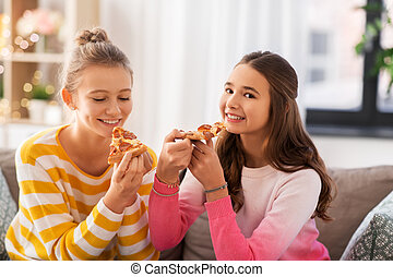 happy teenage girls eating pizza at home