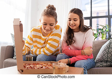 happy teenage girls eating takeaway pizza at home