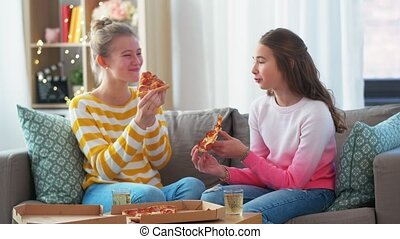 happy teenage girls eating takeaway pizza at home - people, ...