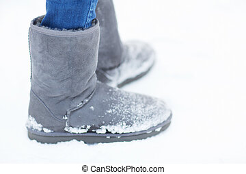 close up of woman legs wearing warm boots on snow