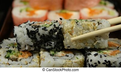 People form the rolls or sushi cooked to order. Close up -...