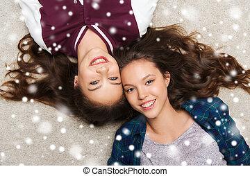 happy smiling pretty teenage girls lying on floor