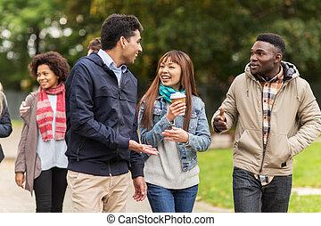 happy friends walking along autumn park