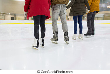 close up of happy friends skating on ice rink