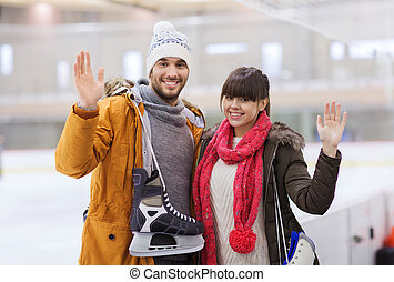 happy couple with ice-skates on skating rink - people,...