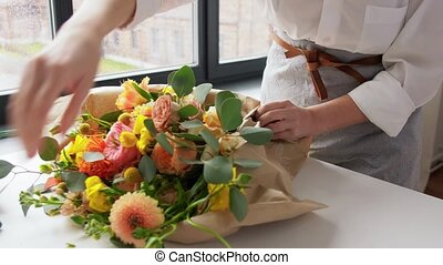 people, gardening and floral design concept - happy woman wrapping flowers to craft paper at home