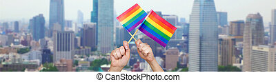 hands holding rainbow flags over city background