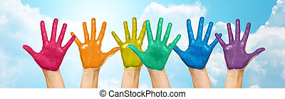 palms of human hands painted in rainbow colors