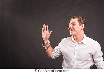 People, gesture and fashion concept - young handsome man waving his hand against brown background with copy space