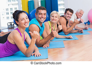 People gesturing thumbs up while lying on mats at gym
