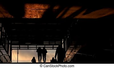 People get out from subway at winter sunset, silhouette
