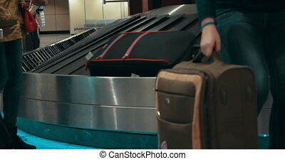 People getting luggage on conveyer belt - People after...