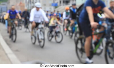People go by bicycles on amateur bike ride in blured