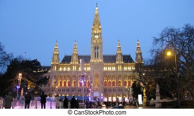 People go for drive on skating rink in front of Rathaus in evening