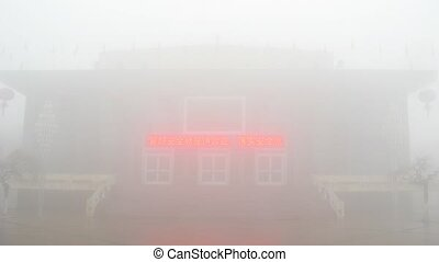 People go near to building in ancient chinese style in fog,...