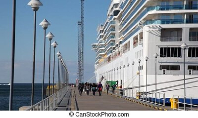 people go on mooring and come into big passenger liner in...