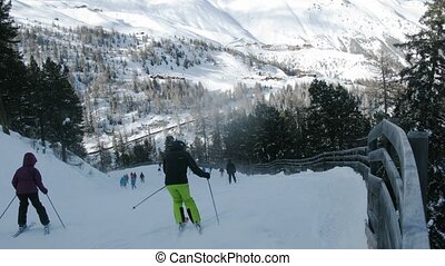 People go on mountain-skiing route downwards where there are...