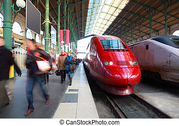 people go on perron, red and gray passenger trains, railway station in Paris, France